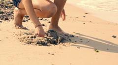 Children play with sand on a beach in summer, vacations, close-up Stock Footage