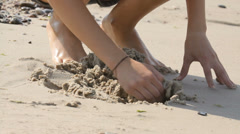 Kid playing with sand in the beach in summer, hands close-up Stock Footage
