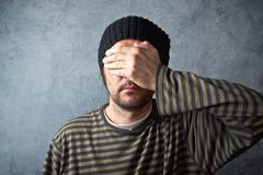 man covering eyes - stock photo
