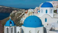 Santorini, Oia Old Town - Slow pan from Japanese bride to blue domed buildings Stock Footage