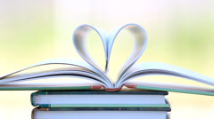 Book stack open page heart shape in wind. - stock footage