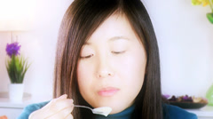 Beauty shot of asian woman eating yogurt slow motion Stock Footage