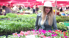 Blonde beautiful woman holding flower in the market Stock Footage