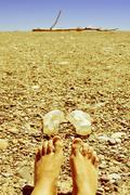 Bare feet in a shingle beach Stock Photos