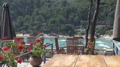 A day at the beach, Greece, red geraniums on terrace, bungalows, sea water Stock Footage