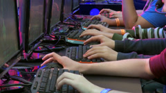 Group of gamers playing online video games, row of computers, hands close up - stock footage