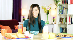Happy asian woman at home having healthy breakfast with cereals and milk Stock Footage