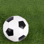 stitch leather soccer focus ball on blur far green grass field. - stock photo