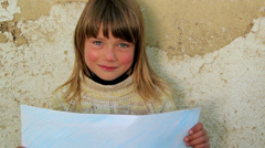 Boy holding a sheet of paper the background of an old wall. Stock Footage