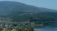 View of the village of Ust-Mana, and a bridge across the taiga river Mana Stock Footage