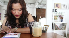 Closeup to Asian girl using app on wi-fi tablet in coffee shop, drinking coffee, Stock Footage