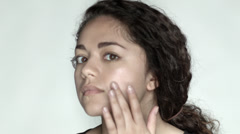 Beautiful Young Woman Applies Facial Cream - stock footage