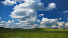 Summer landscape with green grass field and clouds on sky, time-lapse. Stock Footage