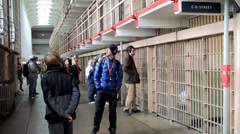 Tourists inside the cellhouse of Alcatraz Island Federal Penitentiary Stock Footage
