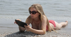Ultra HD 4K Woman work lying sandy beach read text wave sea water ocean digital Stock Footage