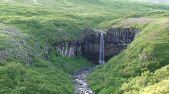 Waterfall in exotic volcanic rock formation Stock Footage