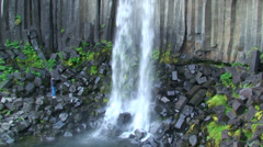 Exotic small waterfall on volcanic rock, tilt from base to brink Stock Footage