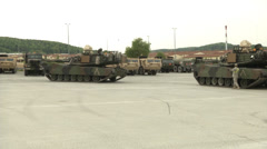 Us army abrams tank guided by soldier to back into place Stock Footage