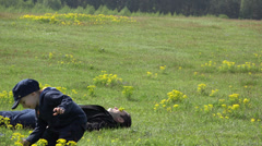 Father and son day, man lay on green grass baby arrange flower on father eyes 4K - stock footage