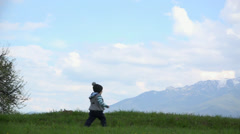 Happy baby running  spring ridge hill, snowed mountains in background, blue sky Stock Footage