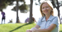 UHD 4K Happy young girl blonde woman smiling looking camera park outdoor relax Stock Footage