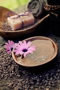 spa and wellness setting with natural soap, candles and towel. violet dayspa - stock photo