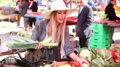 Pretty girl picking leek in the market Stock Footage