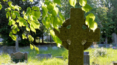 Celtic cross on grave in churchyard Stock Footage