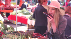 Beautiful girl at the market, picking and smelling eggplants - stock footage