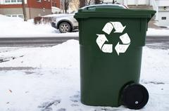 Green recycle bin in front of house during winter Stock Photos
