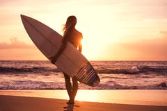 Silhouette surfer girl on the beach at sunset Stock Photos