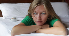 Ultra HD 4K Unhappy woman lying bed home problem financial stress worry pensive - stock footage