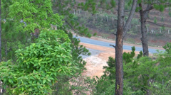 Loaded vehicles passing on a distanced highway in a hilly forest Stock Footage