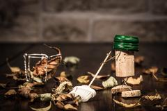 wine cork figures, concept sweeping foliage with a broom - stock photo