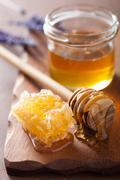 honeycomb dipper and glass jar on wooden background - stock photo