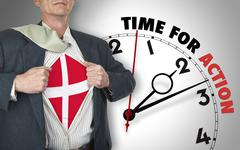 businessman showing shirt with flag from denmark suit against clock - stock illustration