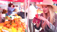 Beautiful girl at the market paying for fruit Stock Footage