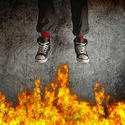 Young man in sneakers is jumping over fire Stock Photos