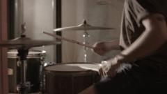 Drummer playing drums in a hallway with camera sweeping past Stock Footage