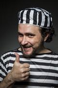 imprisoned, desperate, portrait of a man prisoner in prison garb, over white  - stock photo