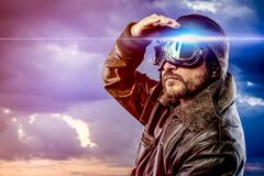 man dressed as pilot in helmet on clouds background. vintage pilot (aviator)  - stock photo