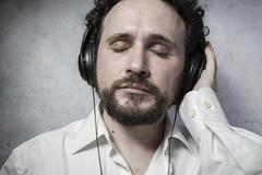 Trendy, listening and enjoying music with headphones, man in white shirt with Kuvituskuvat