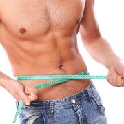 Sexy man measuring his belly after weight lose Stock Photos