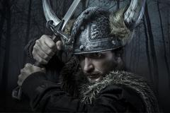 Viking warrior, male dressed in barbarian style with sword, bearded Stock Photos