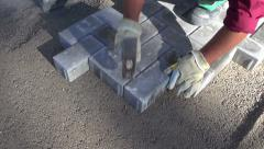 Worker in street fixing  pavement bricks Stock Footage