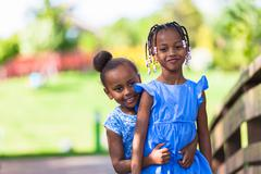 outdoor  portrait of a cute young black sisters - african people - stock photo