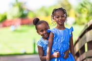 Stock Photo of outdoor  portrait of a cute young black sisters - african people