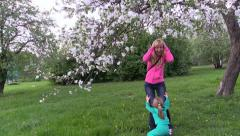 Mom fooling around with daughter and hits head tree blooming apple branch Stock Footage