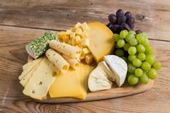 Cheese plate variation on a wooden table Stock Photos