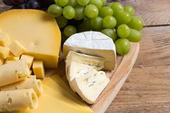 cheese plate variation on a wooden table - stock photo